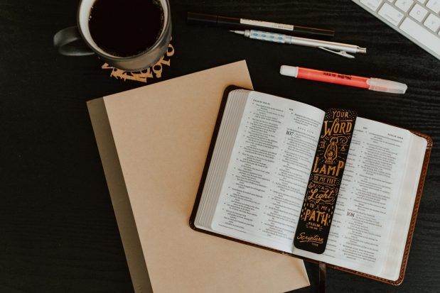 Flat lay image of open Bible, PSalm bookmark, pens, highlighter, a mug of coffee, and a keyboard