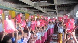 Students holding up their Mon text books