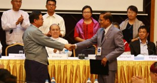 NMSP leader Nai Hongsar (R) shakes hands with government leader U Aung Min (L) after signing a nationwide ceasefire draft agreement, in March 2015 (Photo: RFA).