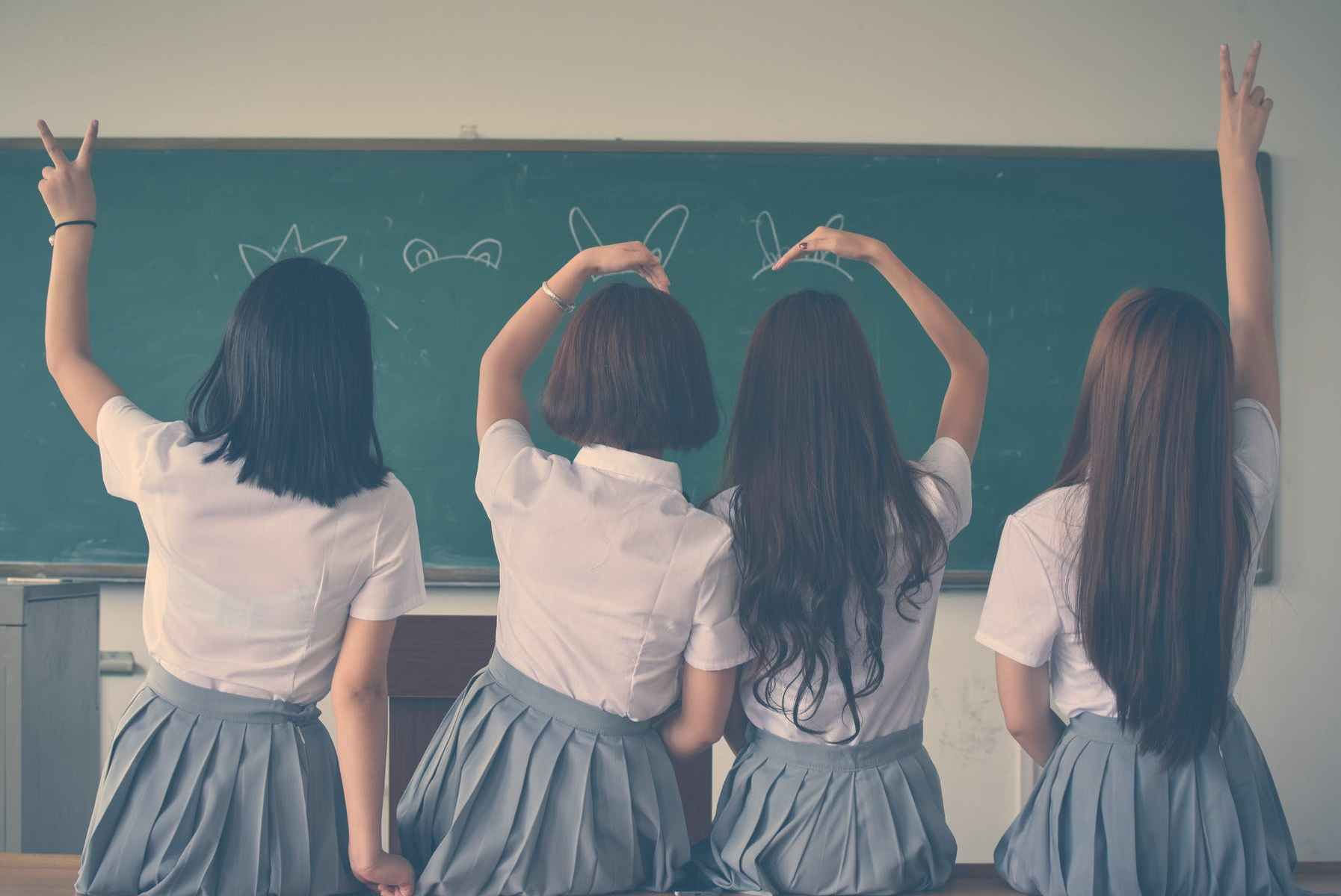 photo of four girls wearing school uniform doing hand signs