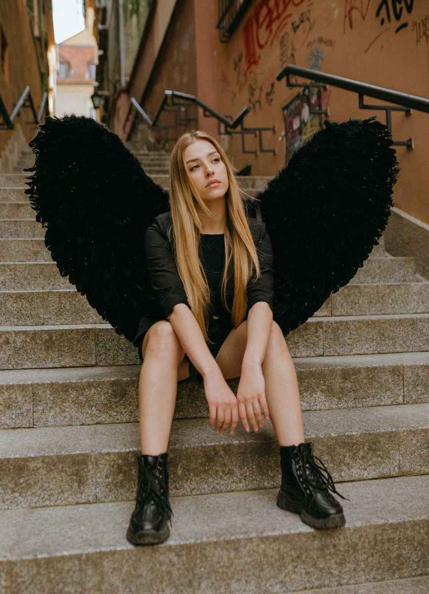 an angel sitting on a staircase