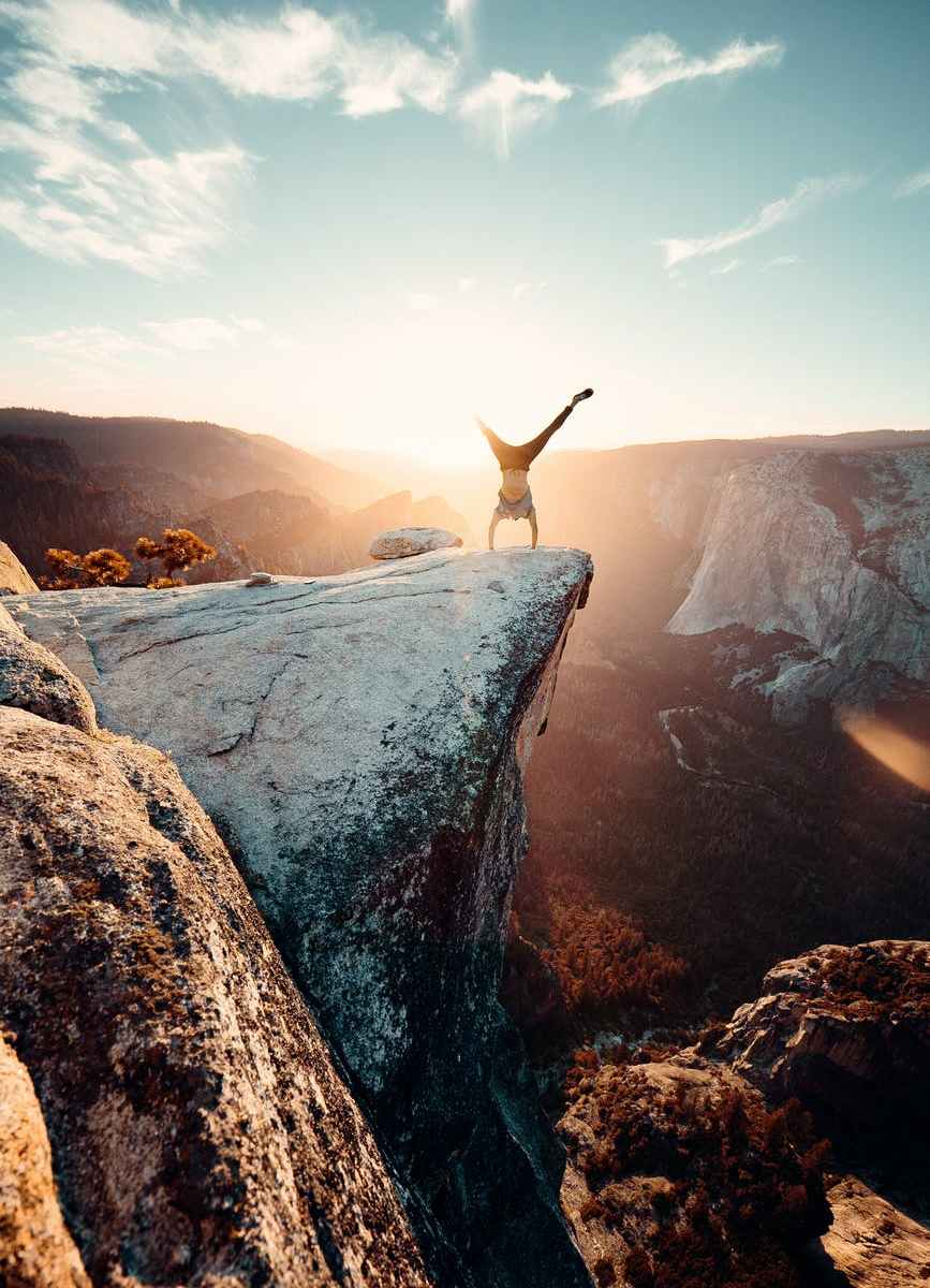 man doing hand stand on mountain