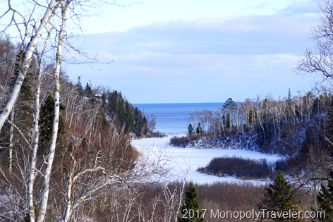 The river is frozen over while Lake Superior remains open in the distance