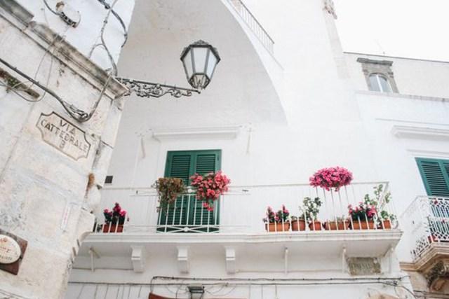 voyage botanique en Italie du haut d'un balcon blanc orné de géranium rose et rouge