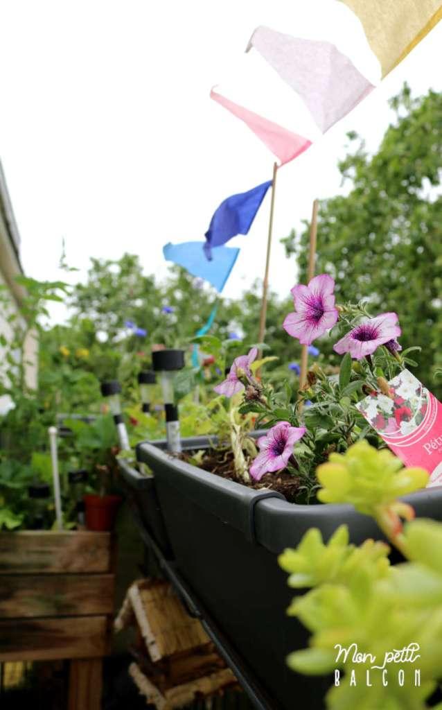 guirlande multicoloe en papier planté dans des jardinières grises, décoration d'un petit balcon et putunia violet et blanc, HEMA
