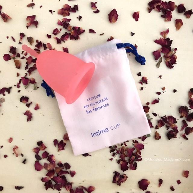 photo de la coupe menstruelle intima et son pochon de tissu, avec pétales de roses.