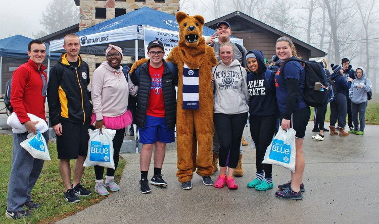 A group of students waits with the Nittany Lion by a tent