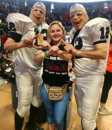 Female THON dancer makes diamond symbols with football player mascots
