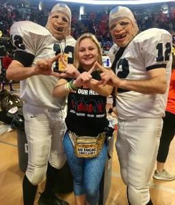 Female THON dancer makes diamond symbols with football player mascots