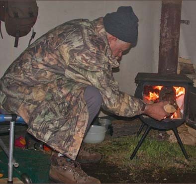 Hunter fueling wood stove in a wall tent.