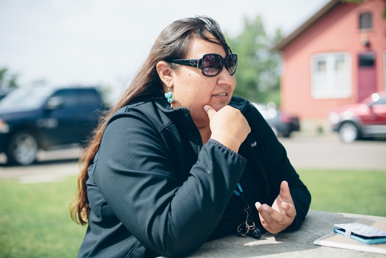 Anti-pipeline activist Angeline Meeks sits at an outdoor table and talks to a reporter.