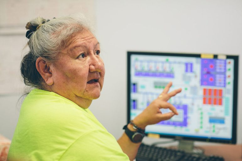 Sandra White Eagle, wearing a yellow shirt, sits in front of a computer and gestures to a reporter as she talks about the threat the Keystone XL pipeline could post to the Fort Peck tribes' water system