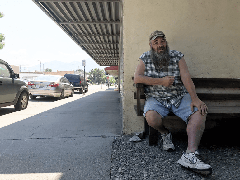 Wes Baker sits on a bench in downtown Livingston, Mont. Baker is on disability and regularly visits the Livingston Food Resource Center to stock up on food.