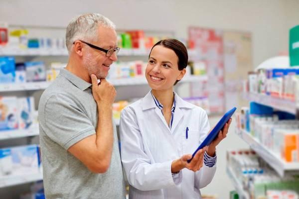 Pharmacist helping senior with prescriptions