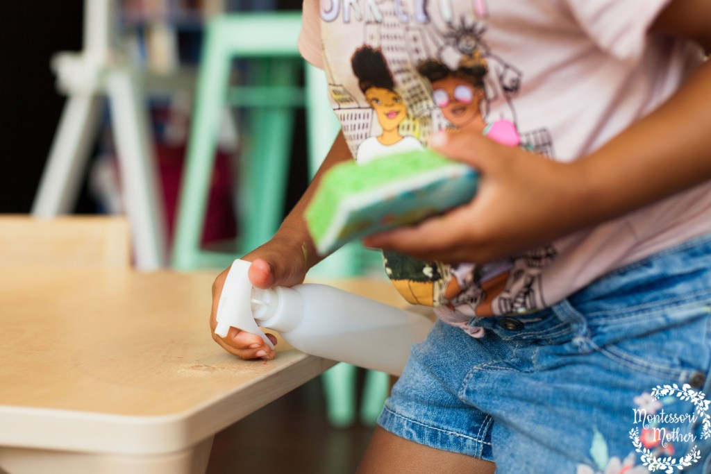 toddler use nienhuis spray bottle to wipe wash montessori table by community playthings