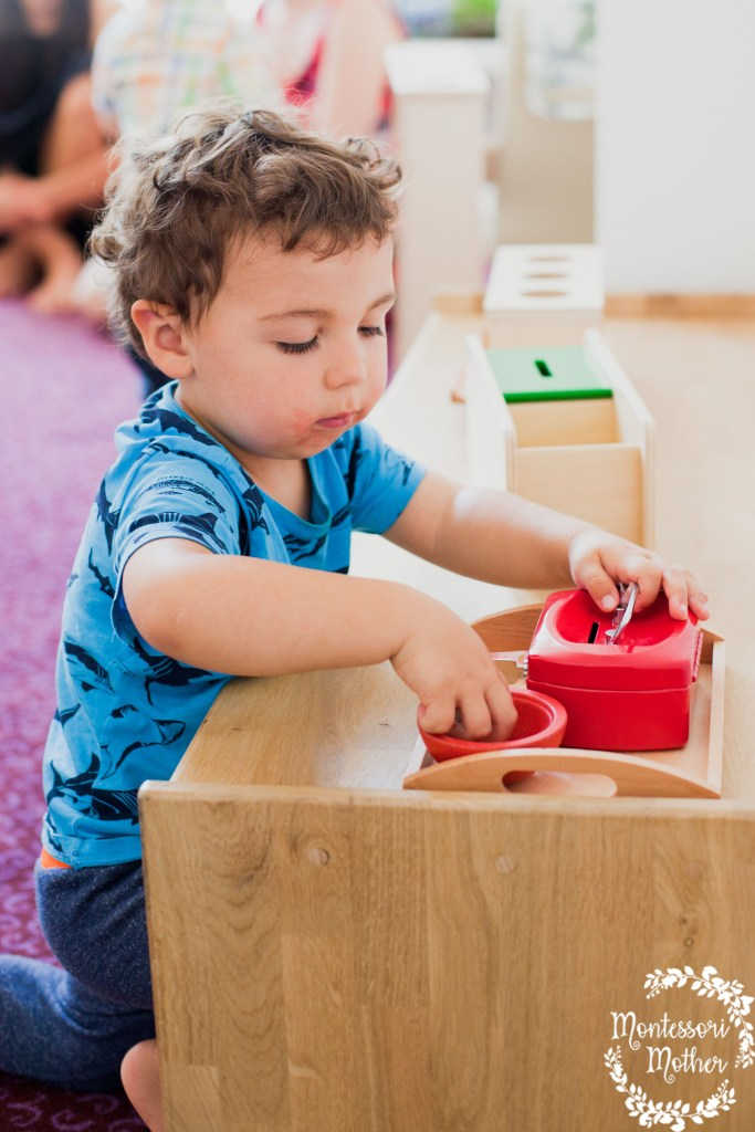 toddler coin box playing at montessori shelf with wooden tray and other learning materials