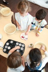 toddler baking day making banana muffins with ikea aprons working together as a group mini muffin trays and banana mashing