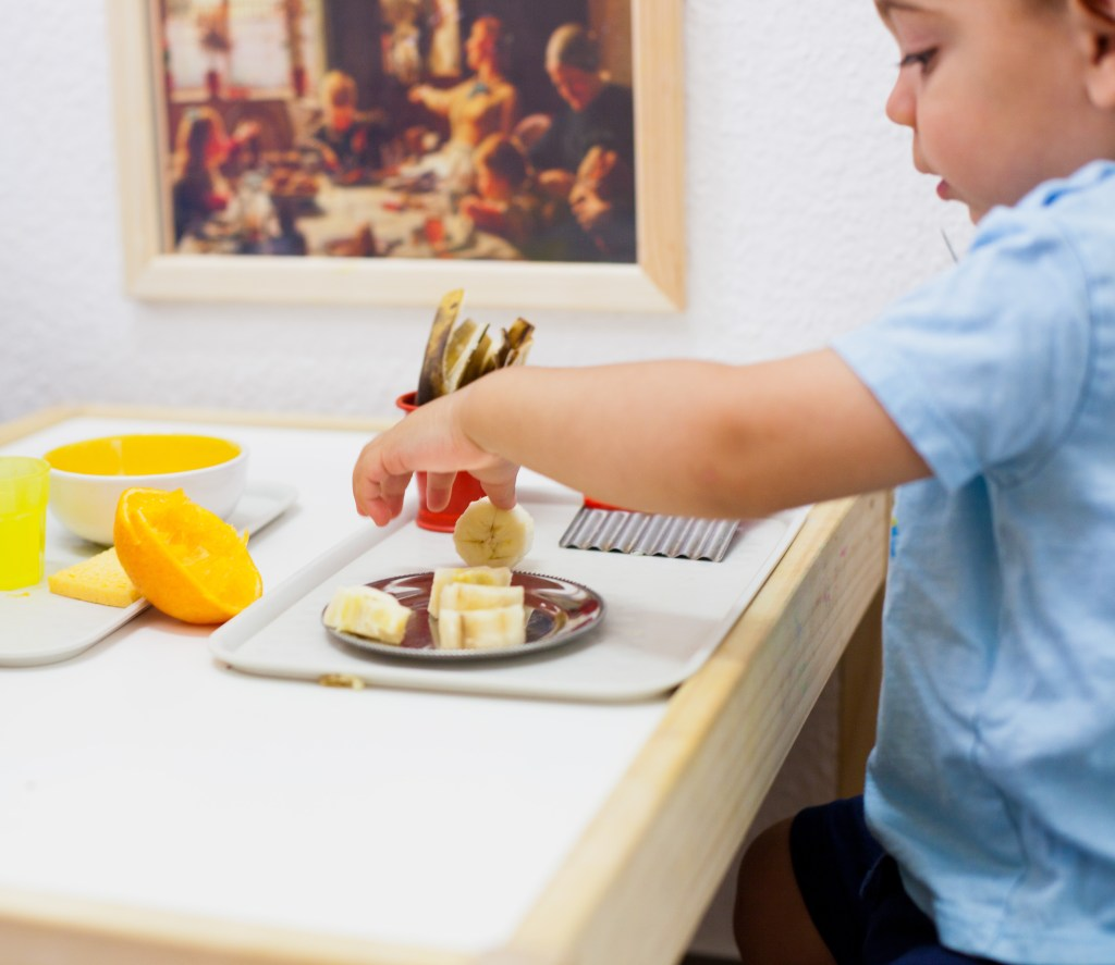 toddler cutting a bamama using a joie crinckle cutter toddler knife in the prepared kitchen area of montessori mother learning center in berlin, germany. This encourages funtional independence and the child can prepare food for himself whenever he feels hungry