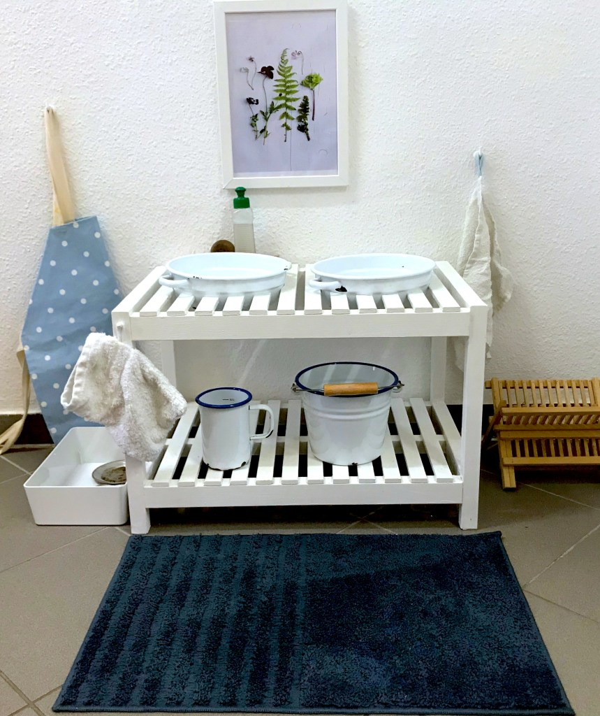 This dishwashing station is one of the montessori practical life tables which we diy made from an ikea bathroom shelf hack, muender email enamel, and montessori design by nuccia polka dot toddler apron. Toddlers wash their own dishes when they want to in the montessori infant community or playgroup and have fun playing with water in a purposeful work way.