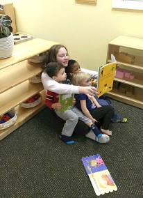 Sixth year student reading to toddlers