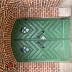 Entrén till skolan. en grön dubbeldörr i den röda tegelbyggnaden.