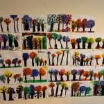 Målningar av träd upphängda på en vägg.