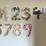 Siffrorna 0 till 9 på väggen där varje siffra har klistrats på med olika material