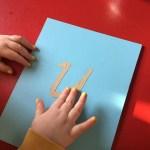 Ett barn känner på bokstaven U som sandpappersbokstav