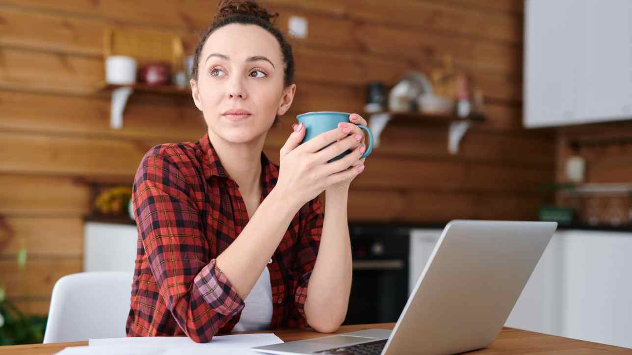 Young pensive freelancer with mug having drink while sitting by kitchen table in front of laptop and getting inspired