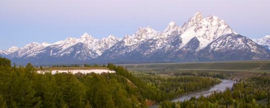 The Grand Tetons standing just beyond the Snake River from the roadside overlook
