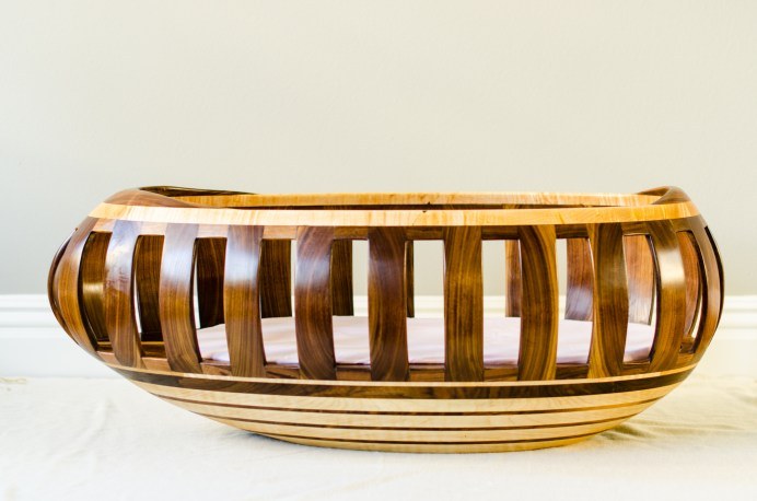 Walnut and maple egg-shaped cradle with bottom compartment