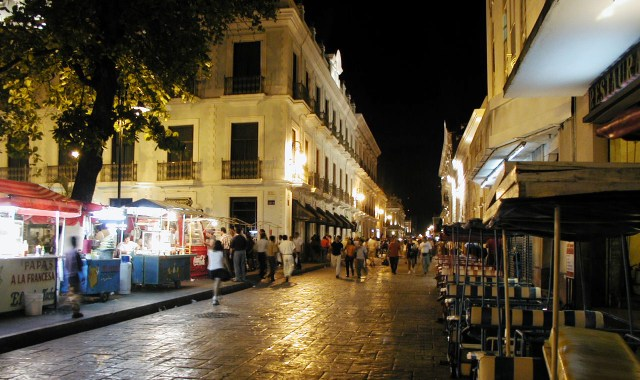 A colonial street at night bustling with shoppers and small market stalls.