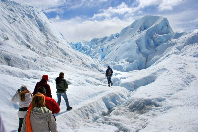 A group of hikers trek across a sculpted frozen landscape.