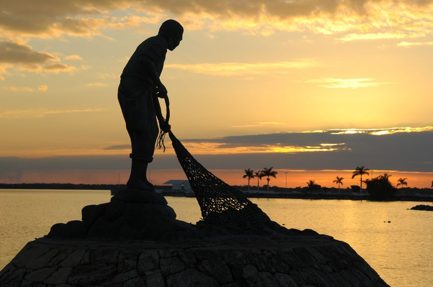 At sunset on the coast, the silhouetted statue of a fisherman hauling in his net.