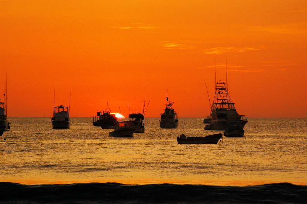 Fishing boats are silhouetted against a vibrant orange sky.