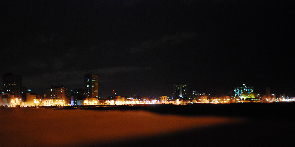 Only the lights of the long strip of buildings along the Malecon are visible.