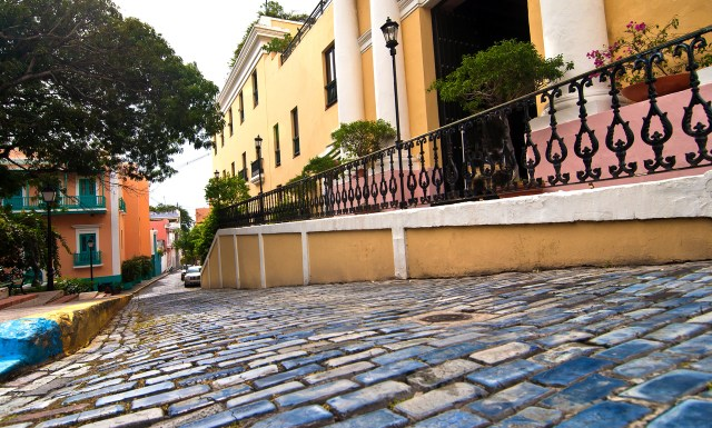 Blue painted cobblestones in the foreground with a row of colonial buildings.