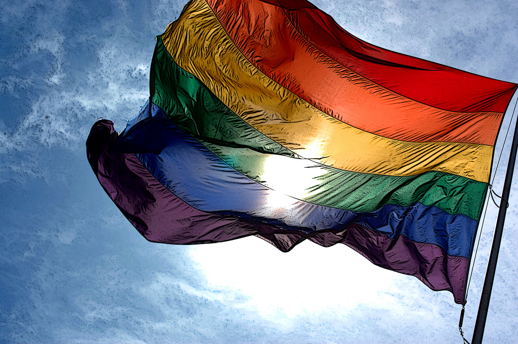 The Rainbow Pride Flag caught in a breeze with the sun behind it.