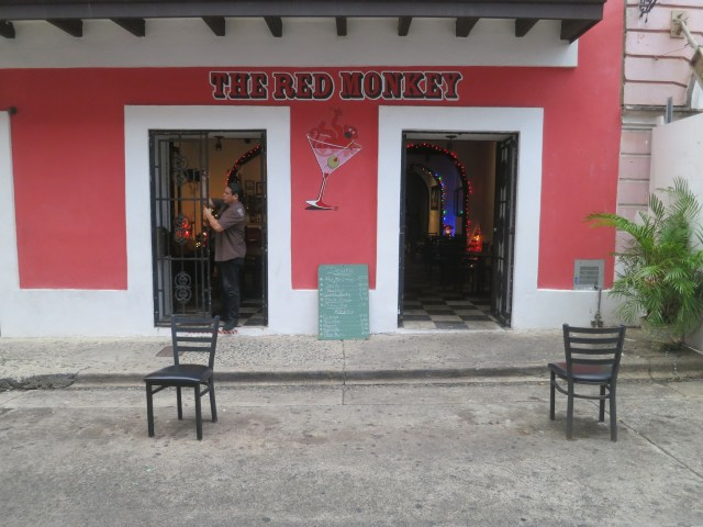 A man stands in the open doorway of the brightly painted Red Monkey bar.