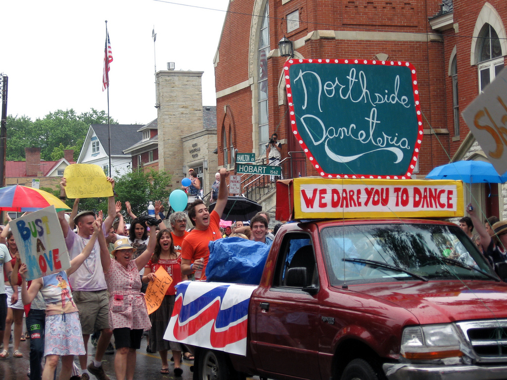 A decorated truck promoting a dance troupe rolls down the parade line.