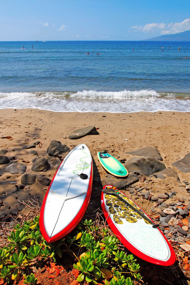 Surf boards in red and white on a Maui beach in Hawaii.