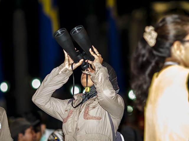 Person with binoculars, looking up