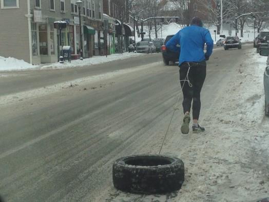 blue shirt running with a tire