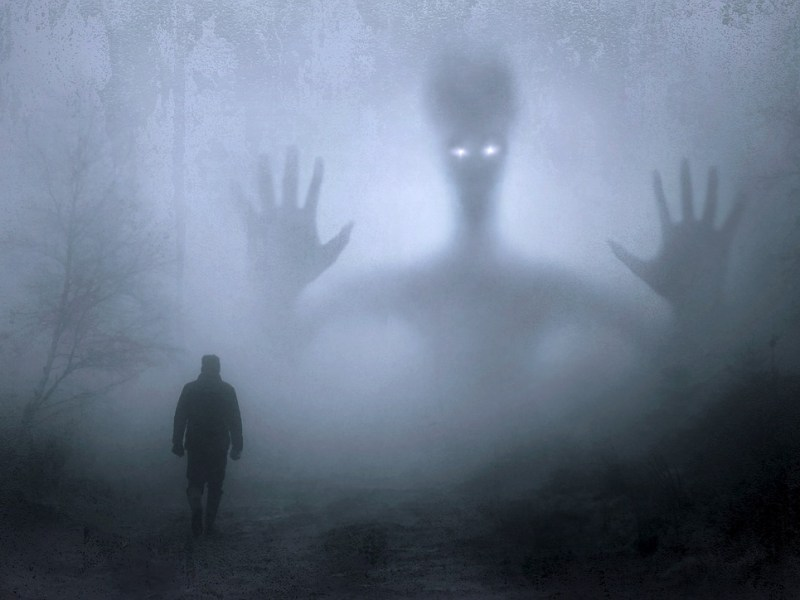 Man meeting monster in creepy forest in the dark night with glowing eyes