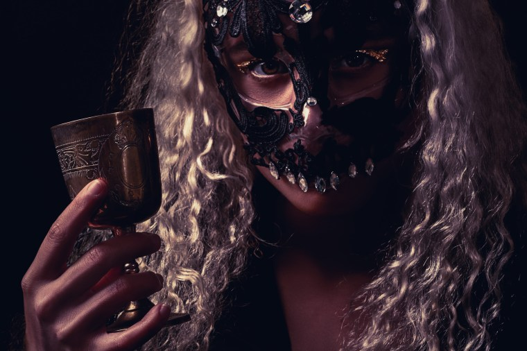 blonde woman in masquerade mask holding a cup