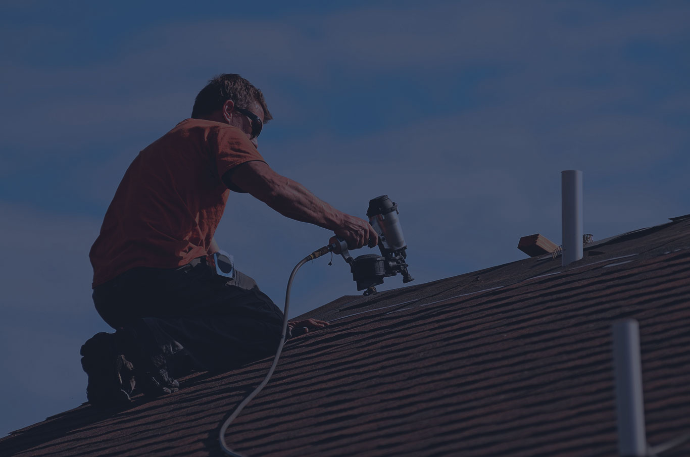 man installing shingle roof with a nail gun