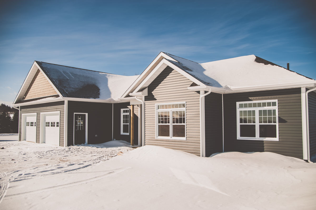 The blue and beige exterior pallet is a wonderful selection for this home. The repeated transom windows add style to this custom home's exterior.