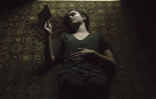 Jovem tumbada en el suelo leyendo un libro