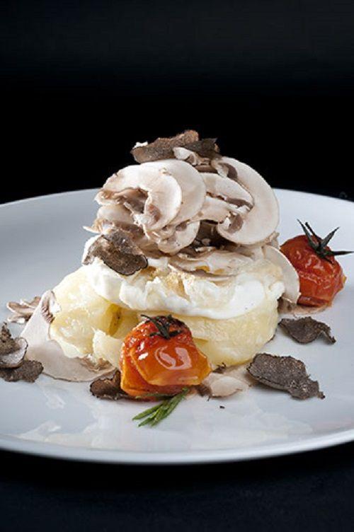 Huevo frito sobre timbal de patata y queso, laminado de champiñones al natual con trufa negra.