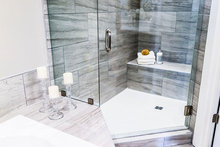 ducha triangular azulejos grises velas blancas